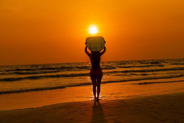 Siluetee al turista asiático joven en bikini con sostener la tabla hawaiana de las manos en la playa y el paisaje marino de la puesta del sol