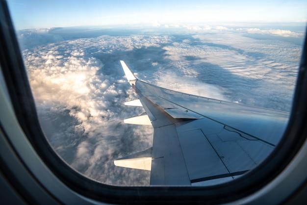 Siluetee el ala de un aeroplano en la opinión de la salida del sol a través de la ventana.