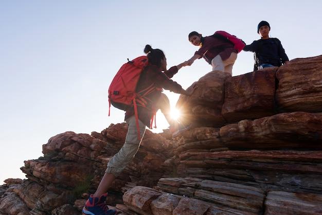 Siluetee a los caminantes masculinos y femeninos que suben el acantilado de la montaña.