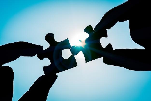 Siluetee la mano de la mujer que conecta una pieza del rompecabezas sobre efecto de la luz del sol.