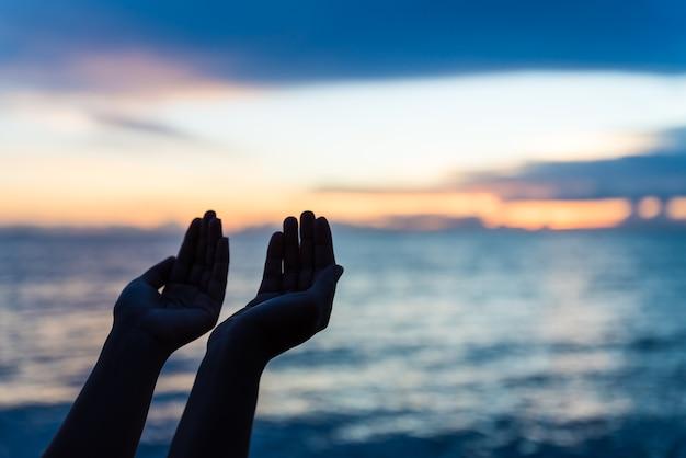 Siluetee las manos de la mujer que ruegan de dios durante puesta del sol, concepto de la esperanza.