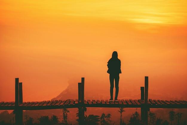 Siluetee a la mujer que se coloca en el puente de madera en la montaña de la colina y el cielo amarillo de la puesta del sol