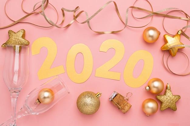 El símbolo del año nuevo, los números 2020 cortados de papel dorado sobre papel rosa de fondo.