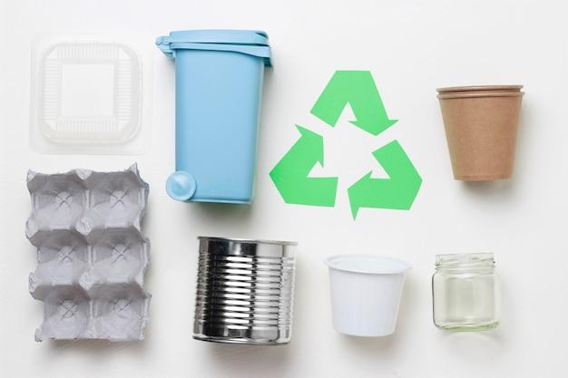 Símbolo de basura de reciclaje verde y plástico, basura de hierro sobre fondo blanco, vista superior.