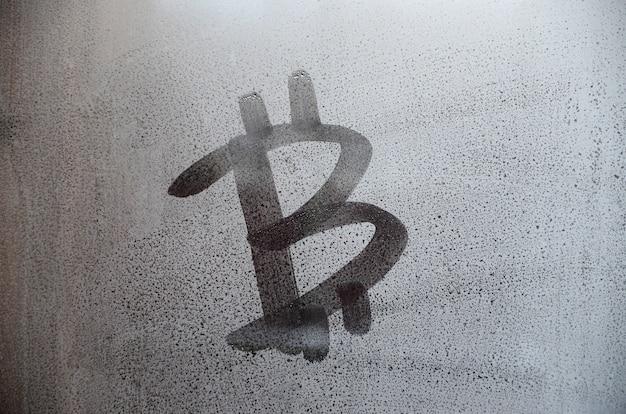 El símbolo de bitcoin en el cristal empañado sudoroso. imagen de fondo abstracto.
