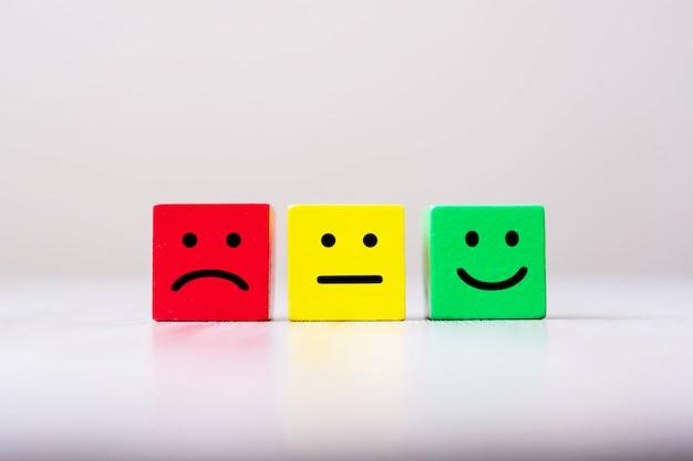 Símbolo de cara de emoción en bloques de cubo de madera. valoración del servicio, clasificación, revisión del cliente, satisfacción y concepto de retroalimentación.
