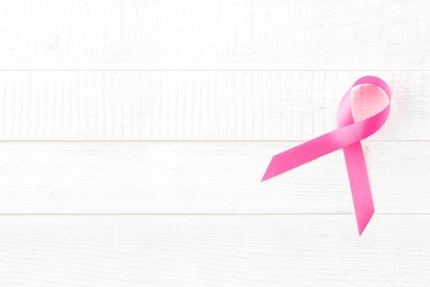 Símbolo de cinta rosa satinada en madera blanca, campaña de concientización sobre el cáncer de mama