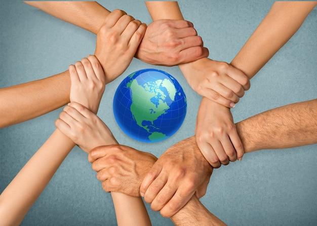 Símbolo conceptual de manos humanas multirraciales que rodean el globo terráqueo. unidad, paz mundial,