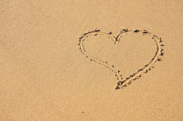 Un símbolo del corazón escrito sobre arena.