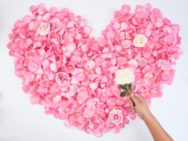 Símbolo de corazón hecho de pétalos de rosa rosa
