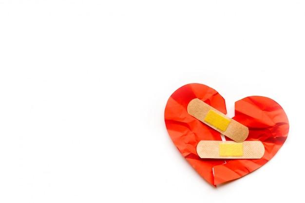 Símbolo de corazón rojo roto con parche médico sobre fondo blanco, concepto de amor. curación