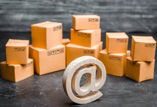 Símbolo de correo electrónico de madera en el fondo de una variedad de cajas. almacén de mercancías