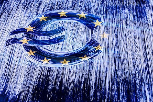 Símbolo del euro sobre un fondo de la bandera de la unión europea. europa. dibujo a mano con pincel. concepto de diseño para negocios y política.1