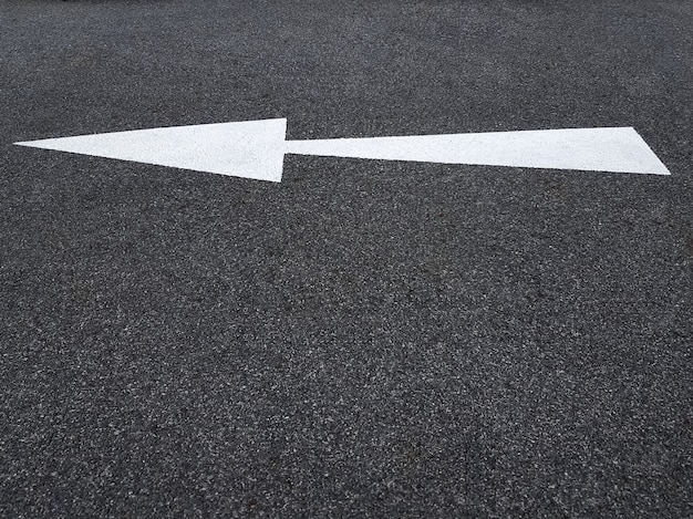 Símbolo de flecha de tráfico blanco en la carretera de asfalto apuntando a la izquierda