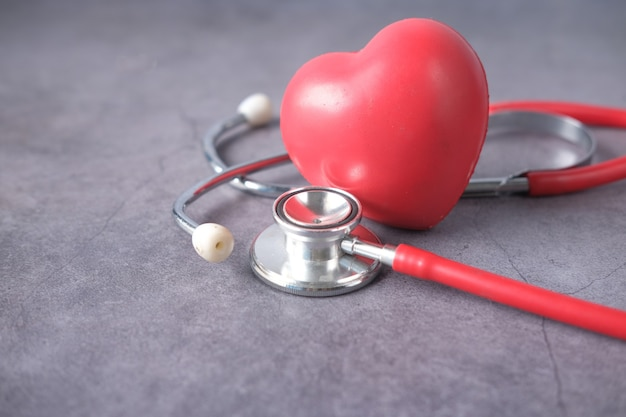 Símbolo de forma de corazón y un estetoscopio sobre fondo blanco.