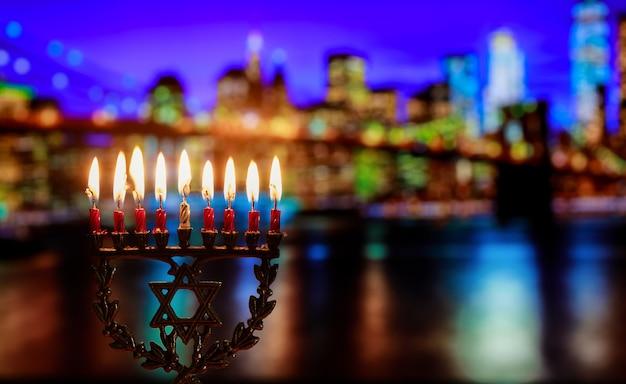 Símbolo de la menorá de janucá de la fiesta tradicional judía puente de brooklyn durante la noche ciudad de nueva york con luces