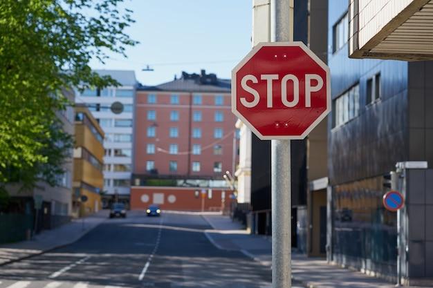 Símbolo de parada con calle borrosa de la ciudad.