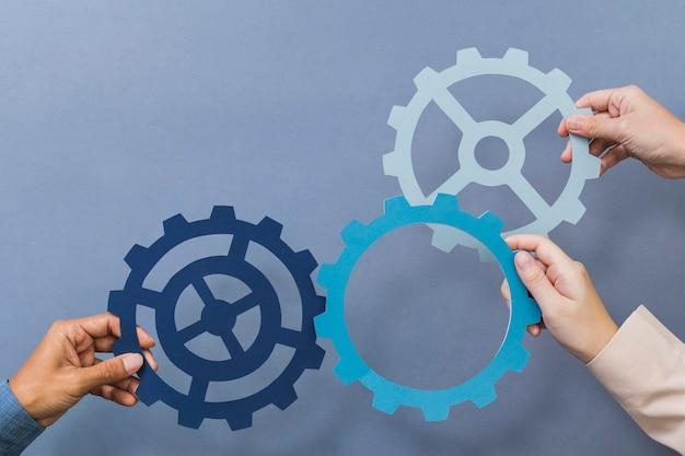Símbolo de productividad empresarial de rueda dentada sostenido por las manos
