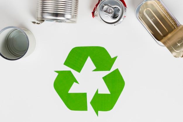 Símbolo de reciclaje al lado de envases metálicos usados.