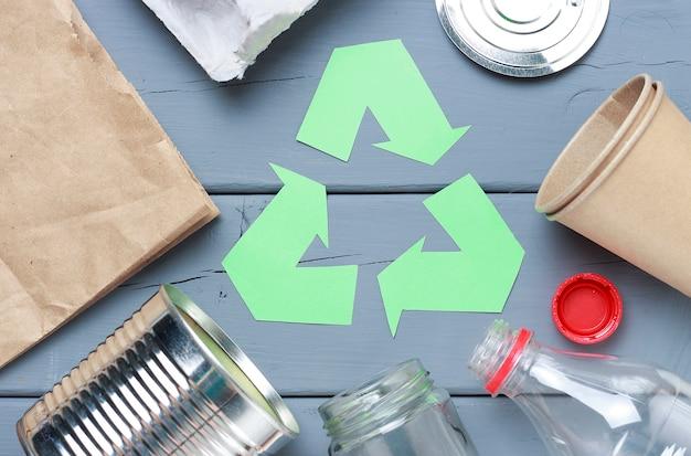 Un símbolo de reciclaje de basura verde y plástico, basura de hierro en un gris