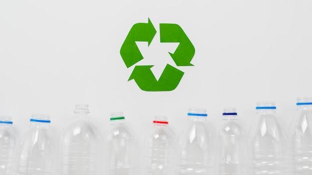 Símbolo de reciclaje y botellas de plástico sobre fondo gris