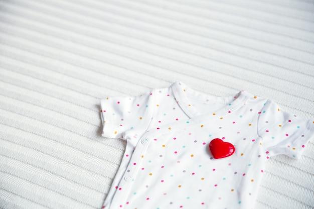 Símbolo de ropa de bebé de corazón sobre fondo de tela blanca.