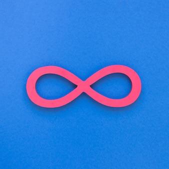 Símbolo rosa infinito sobre fondo azul.