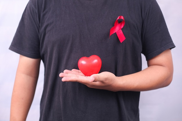 Símbolo del sida con cinta roja contra el vih aislado sobre fondo blanco.
