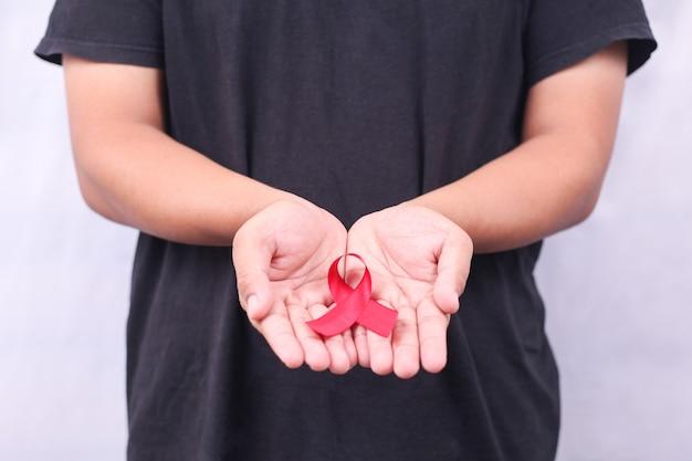 Símbolo del sida con cinta roja en mano aislado sobre fondo blanco.