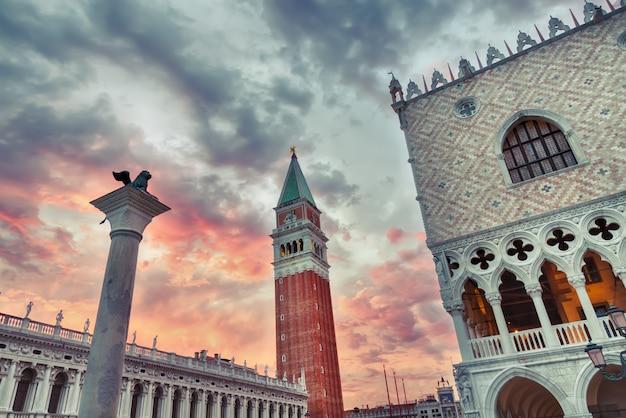 Símbolo de venecia león, san marco campanile y palacio ducal con cielo dramático rojo durante la puesta de sol. monumentos de venecia de fama mundial