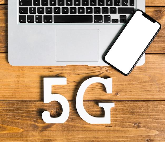 Símbolos 5g y dispositivos electrónicos en mesa.