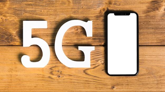 Símbolos 5g y smartphone en escritorio.