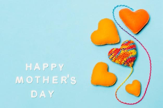 Símbolos decorativos del corazón cerca de la inscripción del día de las madres felices