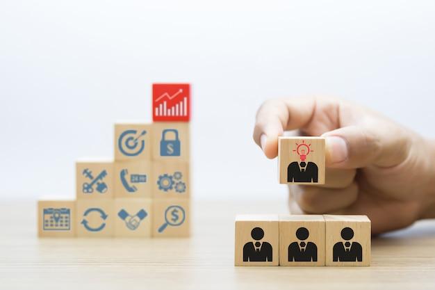 Símbolos de personas y negocios con bloque de madera.