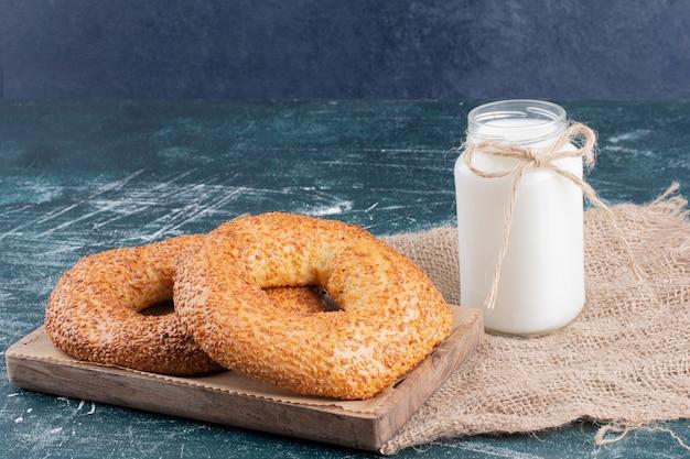 Simit bagels con sésamo y tarro de leche en azul.