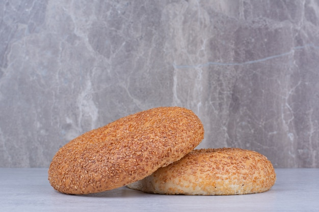 Simits turcos con semillas de sésamo sobre mesa de mármol.