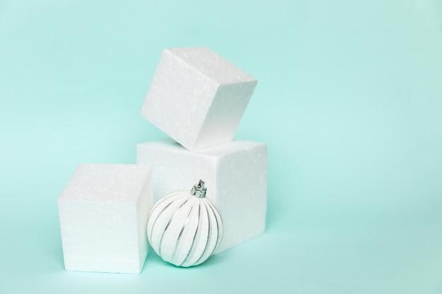 Simplemente composición mínima ornamento de objeto de invierno y formas de cubo forma geométrica podio aislado fondo azul pastel. navidad año nuevo diciembre tiempo por concepto de celebración. maqueta, espacio de copia
