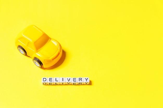 Simplemente diseñe el coche de juguete amarillo y la palabra entrega de la inscripción aislada en el fondo colorido amarillo