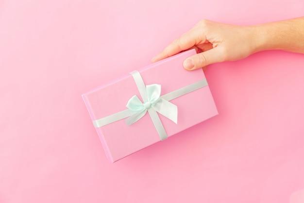 Simplemente diseñe la mano femenina de la mujer que sostiene la caja de regalo rosada aislada en fondo de moda colorido en colores pastel rosado