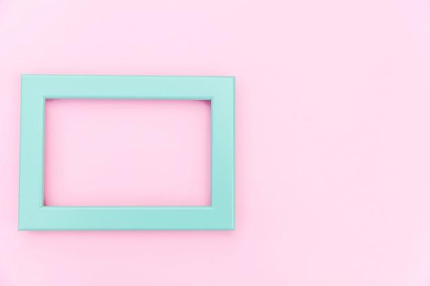 Simplemente diseñe con el marco azul vacío aislado sobre fondo de colores pastel rosa. vista superior, plano, copia espacio, maqueta. concepto mínimo.