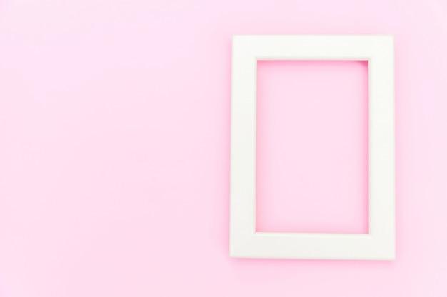 Simplemente diseñe con el marco rosado vacío aislado en el fondo colorido en colores pastel rosado. vista superior, plano, copia espacio, maqueta. concepto mínimo.