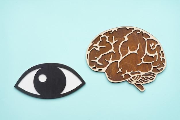 Simulacro de ojo y cerebro de madera sobre fondo azul.
