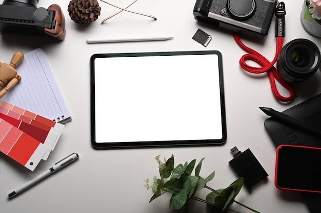 Simulacros de accesorios de cámara y tableta digital en mesa blanca.