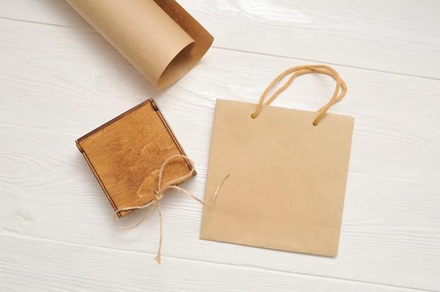 Simulacros de bolsa de papel para manualidades y caja de madera sobre mesa vintage de madera blanca