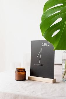 Simulacros de carpa de mesa con palabras tabla 1 en mesa de restaurante con ramo tropical. carpa de mesa de tiza negra
