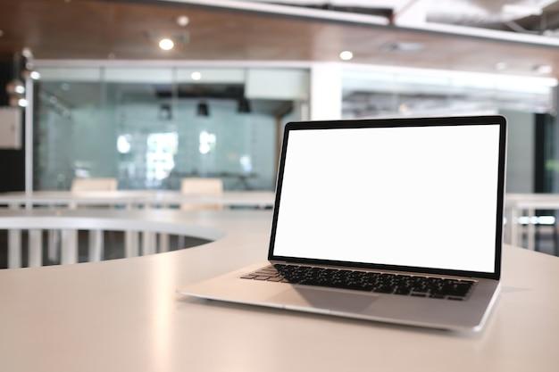 Simulacros de computadora portátil de pantalla en blanco con pantalla blanca en un escritorio de madera en la habitación de moern.