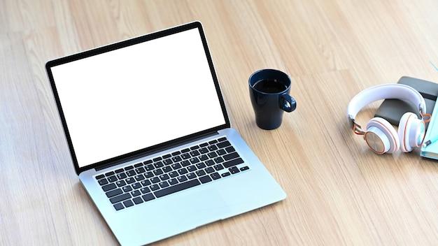 Simulacros de computadora portátil, taza de café, auriculares y portátil en un piso de madera.