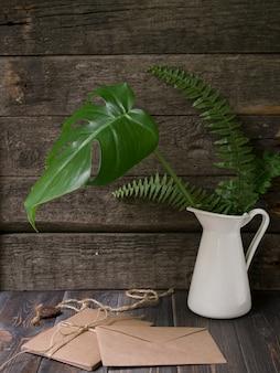 Simulacros de espacio de trabajo con hojas tropicales en jarrón y sobres artesanales sobre fondo de madera