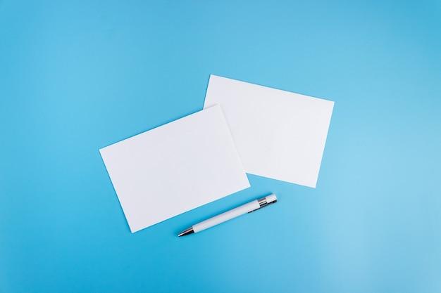 Simulacros de una hoja en blanco sobre un fondo azul con un bolígrafo. plantilla de papel para el diseño. tarjeta de visita. endecha plana, copie el espacio.