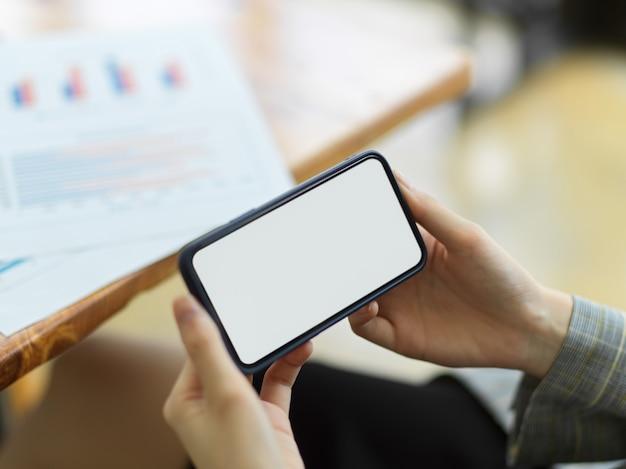 Simulacros de imagen de la mano femenina sosteniendo un teléfono inteligente móvil horizontal con pantalla en blanco. fondo borroso. juego, aplicación, ver el concepto de video